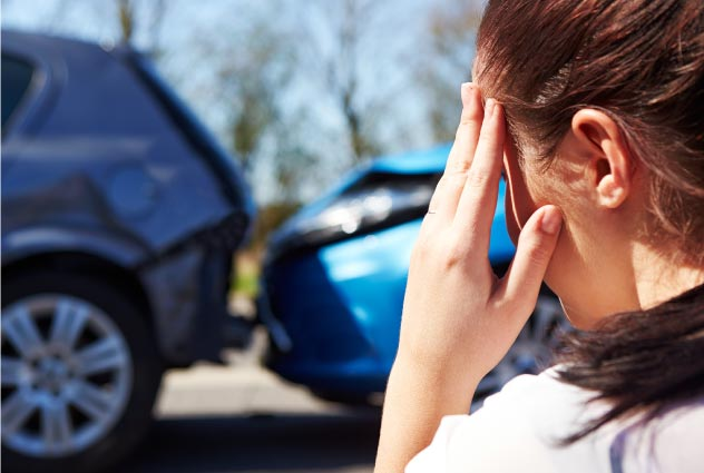 stressed woman with car accident in front of her | Luis Guerra Personal Injury Trial Attorneys | Phoenix, Arizona