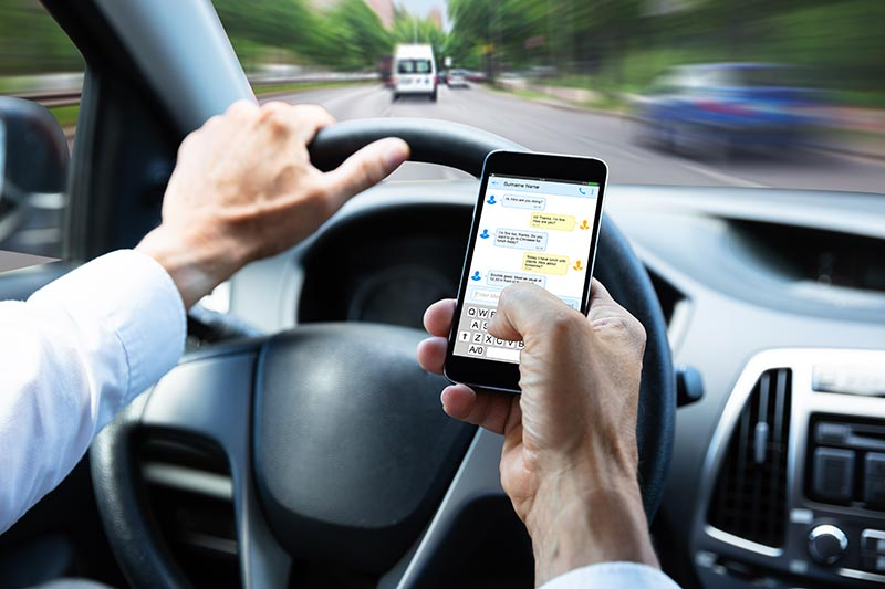 man driving while texting | Luis Guerra Personal Injury Trial Attorneys | Phoenix, Arizona