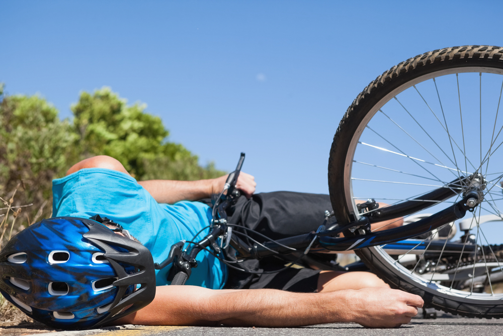 cyclist fallen off the ground with bike | Luis Guerra Personal Injury Trial Attorneys | Phoenix, Arizona