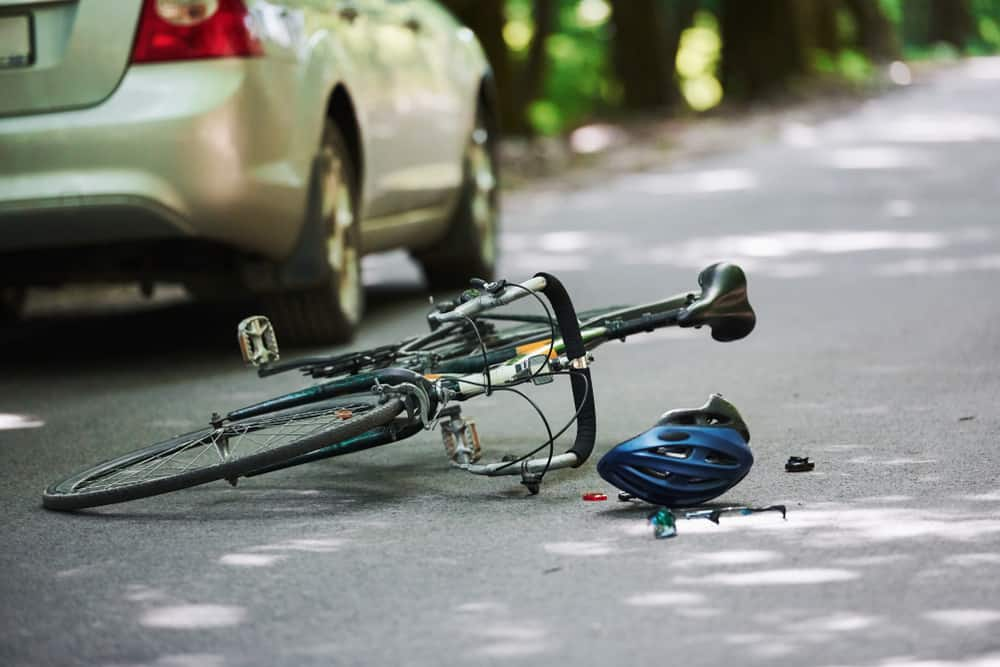 fallen bike with helmet and car | Luis Guerra Personal Injury Trial Attorneys